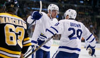 Toronto Maple Leafs' Connor Brown (28) celebrates his goal with teammate Auston Matthews as Boston Bruins' Brad Marchand (63) looks on during the first period of Game 5 of an NHL hockey first-round playoff series in Boston, Saturday, April 21, 2018. The Maple Leafs won 4-3. (AP Photo/Michael Dwyer)