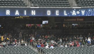 Fans stay dry under a deck in the stands during a rain delay in the start of baseball game against the New York Mets at the Atlanta Braves SunTrust Park Sunday, April 22, 2018, in Atlanta. (AP Photo/John Amis)