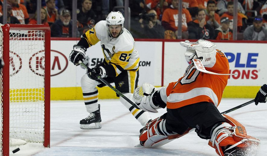 Pittsburgh Penguins' Sidney Crosby, left, scores past Philadelphia Flyers' Michal Neuvirth during the first period in Game 6 of an NHL first-round hockey playoff series Sunday, April 22, 2018, in Philadelphia. (AP Photo/Tom Mihalek)