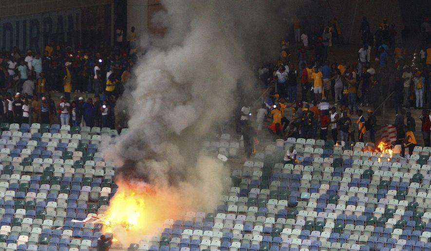 A fire burns in the stands at the Moses Mabhida stedium in Durban, South Africa, Saturday, April 21, 2018, after violence broke out at a soccer game when hundreds of fans ripped up parts of the stadium, invaded the pitch, and assaulted at least one security guard. The incident occurred after the Kaizer Chiefs lost 2-0 to Free State Stars in the semifinals of the Nedbank Cup competition. (AP Photo/Bongani Mbatha - African News Agency)