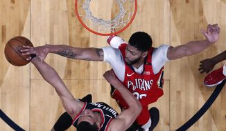 New Orleans Pelicans forward Anthony Davis blocks a shot by Portland Trail Blazers guard Wade Baldwin IV during the first half of Game 4 of a first-round NBA basketball playoff series in New Orleans, Saturday, April 21, 2018. (AP Photo/Scott Threlkeld)