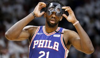 Philadelphia 76ers center Joel Embiid (21) adjusts his mask in the third quarter of play against the Miami Heat in Game 4 of a first-round NBA basketball playoff series, Saturday, April 21, 2018, in Miami. (AP Photo/Joe Skipper)