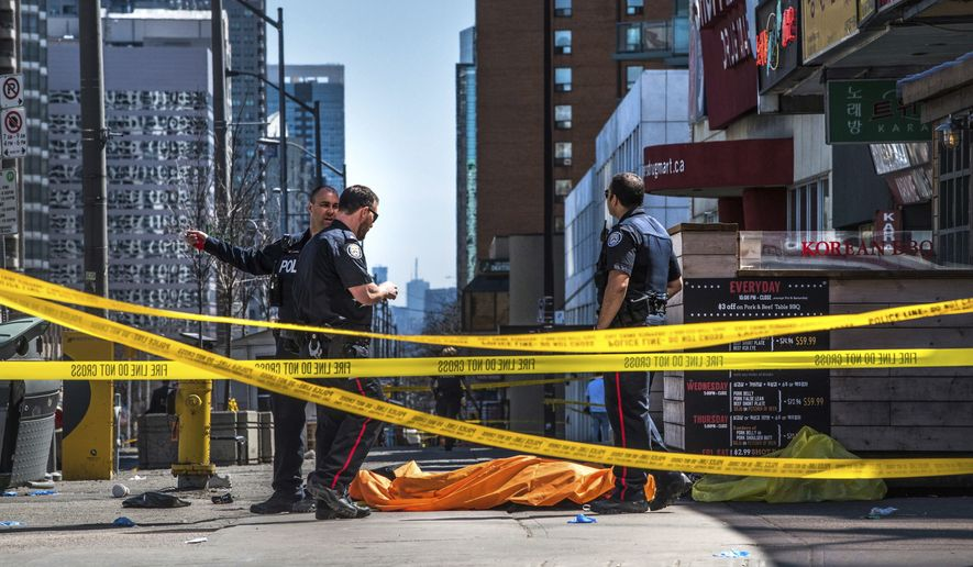 28e32bd7c84386 Police officers stand by a covered body in Toronto after a van mounted a  sidewalk and