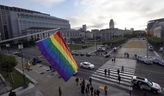 A rainbow flag hangs from the office of San Francisco Mayor Ed Lee at City Hall Wednesday, June 26, 2013.  The Supreme Court on Wednesday struck down a provision of a U.S. law denying federal benefits to married gay couples and cleared the way for the resumption of same-sex marriage in the state of California. The justices issued two 5-4 rulings in their final session of the term. One decision wiped away part of a federal anti-gay marriage law that has kept legally married same-sex couples from receiving tax, health and pension benefits. The other was a technical legal ruling that said nothing at all about same-sex marriage, but left in place a trial court's declaration that California's Proposition 8 is unconstitutional. (AP Photo/Jeff Chiu)