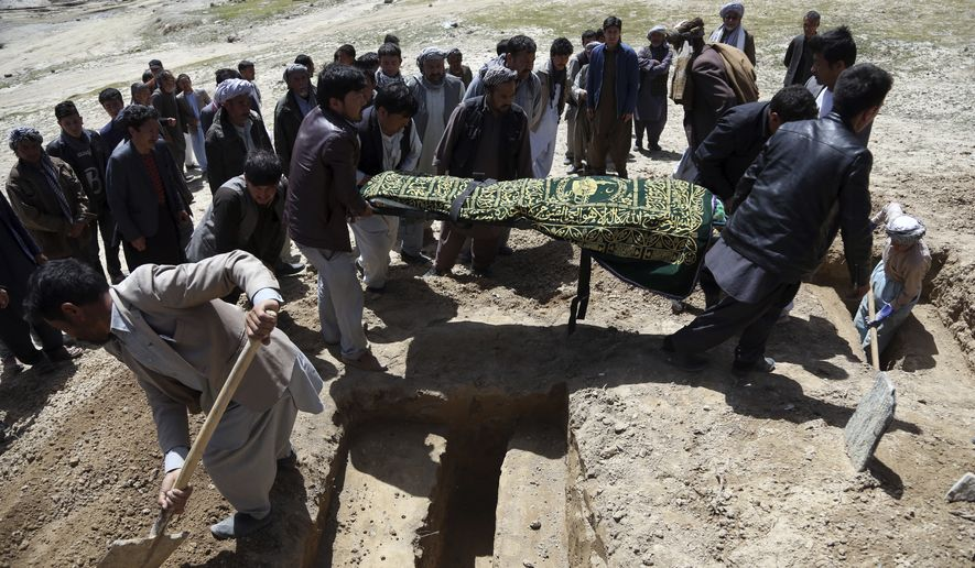 Afghan men bury a victim of Sunday's suicide attack at a voter registration center, in Kabul, Afghanistan, Monday, April 23, 2018. Taliban attacks in western Afghanistan killed 14 soldiers and policemen on Monday as residents in the capital, Kabul, prepared for the funerals of those killed in the horrific bombing by the Islamic State group on a voter registration center that left at least 57 dead the previous day. (AP Photo/Rahmat Gul)