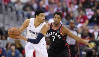 Washington Wizards forward Otto Porter Jr. (22) handles the ball against Toronto Raptors guard Kyle Lowry (7) during the first half of Game 4 of an NBA basketball first-round playoff series, Sunday, April 22, 2018, in Washington. (AP Photo/Nick Wass)