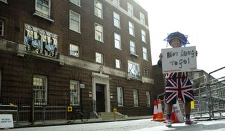 """FILE - In this Friday, April 24, 2015 file photo, Terry Hutt poses for the media with a sign that reads 'Not Long to Go' as he waits with other royal fans, outside the Lindo wing at St Mary's Hospital in London.  Kensington Palace says Prince William's wife, the Duchess of Cambridge has entered a London hospital to give birth to the couple's third child. The former Kate Middleton traveled by car on Monday, April 23, 2018 to the private Lindo Wing of St. Mary's Hospital in central London. The palace says she was in """"the early stages of labor."""" (AP Photo/Alastair Grant, File)"""