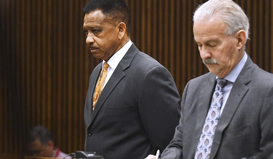 Detroit Police Officer Lonnie Wade, left, with Lawyer Steven Fishman, is sentenced in the court room of Wayne County Judge Mariam Bazzi at Frank Murphy Hall of Justice in Detroit, on April Monday, 23, 2018. Wade, accused of assaulting a shopper at a store while moonlighting as a security guard has been sentenced to three years of probation. (Daniel Mears/Detroit News via AP)