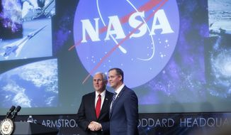 Vice President Mike Pence, left, shakes hands with the new NASA administrator Jim Bridenstine, right, on stage during a swearing-in ceremony, Monday, April 23, 2018, at NASA Headquarters in Washington. (AP Photo/Pablo Martinez Monsivais)
