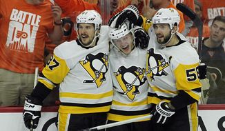 From left to right, Pittsburgh Penguins' Sidney Crosby, Jake Guentzel and Kris Letang celebrate Guentzels' goal during the third period in Game 6 of an NHL first-round hockey playoff series Sunday, April 22, 2018, in Philadelphia. (AP Photo/Tom Mihalek)