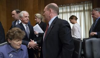 "Senate Foreign Relations Committee Chairman Bob Corker, R-Tenn., center left, reaches to shake hands with Sen. Chris Coons, D-Del., with Sen. Jeanne Shaheen, D-N.H., seated lower left, to end a dramatic vote for President Donald Trump's nominee for secretary of state, Mike Pompeo, who has faced considerable opposition before the panel, on Capitol Hill in Washington, Monday, April 23, 2018. When the Republicans on the panel were missing a ""yes"" vote by Sen. Johnny Isakson, R-Ga., who was late returning to Washington after giving a eulogy for a friend, Sen. Coons, a Democrat, offered to vote ""present"" to get the Pompeo nomination to the floor favorably even though he opposed it. (AP Photo/J. Scott Applewhite)"