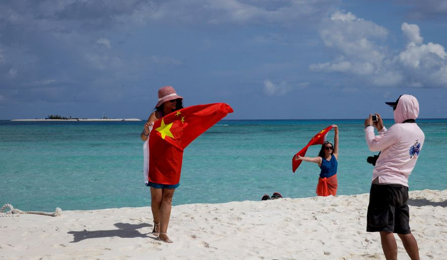 In this Sept. 14, 2014, file photo, Chinese tourists take souvenir photos with a Chinese national flag as they visit Quanfu Island, one of Paracel Islands of Sansha prefecture of southern China's Hainan province in the South China Sea. (AP Photo/Peng Peng, File)