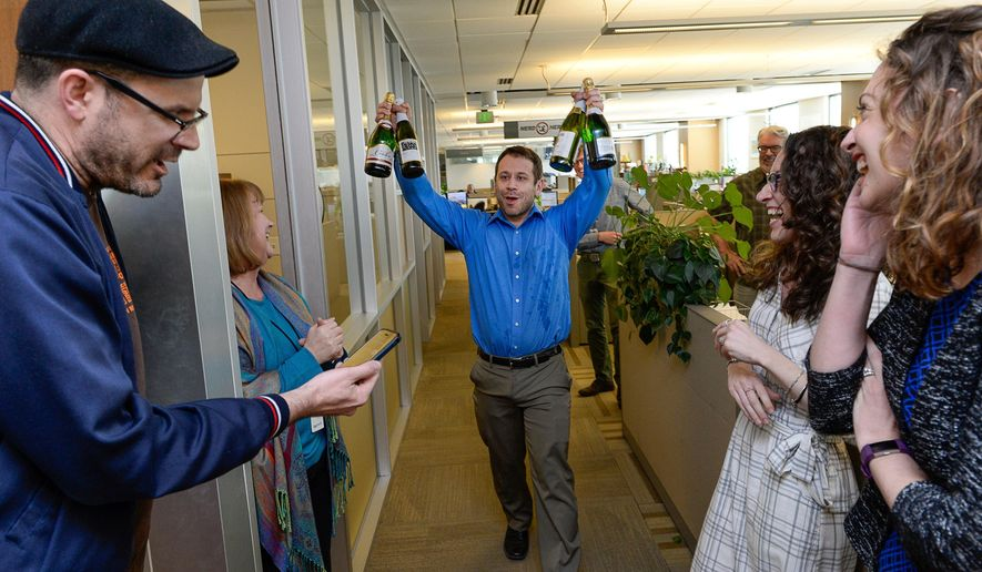 FILE - In this April 10, 2017, file photo, the Salt Lake Tribune Editor Matt Canham breaks out the champagne after their 2017 Pulitzer Prize for local reporting was announced, in Salt Like City. The Tribune newsroom takes up one floor of the building that bears its name, overlooking snow-capped mountains and the arena where the Utah Jazz play. Once a Digital First property that dealt with staff reductions and feared closure, the paper was sold to a prominent local family in 2016. Since then, its reporters received their first raise in a decade and won a Pulitzer prize for investigative reporting.  (Francisco Kjolseth/The Salt Lake Tribune via AP, File)