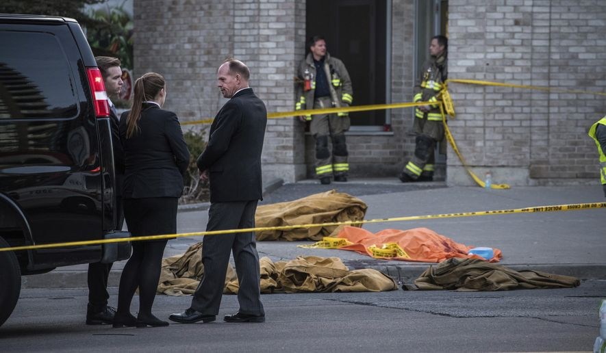 A coroner waits to remove a dead body from the sidewalk after a driver plowed a rented van along a crowded sidewalk, killing multiple people and injuring others, Monday, April 23, 2018, in Toronto. (Aaron Vincent Elkaim/The Canadian Press via AP)