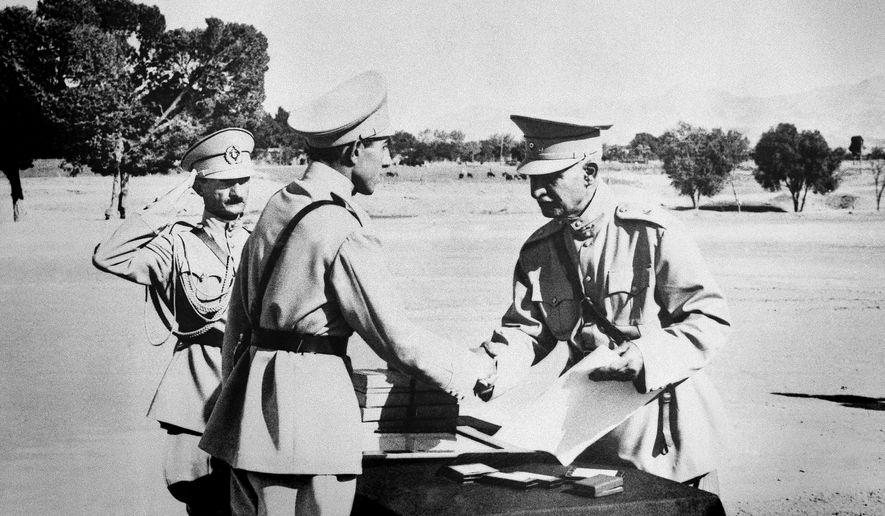 """In this August 19, 1941 file photo, Reza Shah Pahlavi, hands second son, Ali Reza, commission as officer at graduation exercises at Iran's """"West Point"""" in Tehran, Iran prior to Anglo-Russian action. The discovery in Iran of a mummified body near the site of a former royal mausoleum has raised speculation it could be the remains of the late Reza Shah Pahlavi, founder of the Pahlavi dynasty.  (AP Photo, File)"""