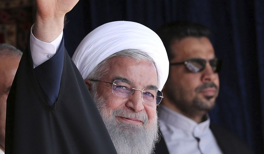 In this photo released by official website of the office of the Iranian Presidency, President Hassan Rouhani waves to the crowd in a public gathering during his visit to the northwestern city of Tabriz, Iran, Tuesday, April 24, 2018. Iran's president reiterated his warning against a U.S. pullout from the landmark nuclear deal between Tehran and world powers as meetings between President Donald Trump France's Emmanuel Macron got underway in Washington. (Iranian Presidency Office via AP)