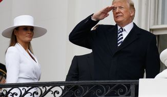 President Donald Trump, joined by first lady Melania Trump, salutes from the Truman Balcony during a State Arrival Ceremony at the White House in Washington, Tuesday, April 24, 2018, in honor of French President Emmanuel Macron and his wife Brigitte Macron. (AP Photo/Carolyn Kaster)