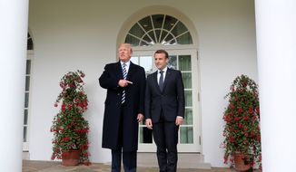 President Donald Trump points toward French President Emmanuel Macron as they walk along the White House colonnade after a State Arrival Ceremony on the South Lawn in Washington, Tuesday, April 24, 2018. (AP Photo/Pablo Martinez Monsivais)