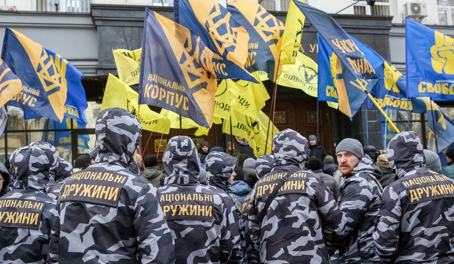 Feb. 1, 2018 - Kiev, Ukraine - National Militia fighters hold flags from the National Corpus nationalistic political party and Azov Movement during a protest. By Konstantin Chernichkin/Special to The Washington Times