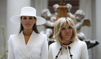 First lady Melania Trump, left, and Brigitte Macron, wife of French President Emmanuel Macron, pause for a photograph together as they tour the National Gallery of Art, Tuesday April 24, 2018, in Washington. (AP Photo/Jacquelyn Martin)
