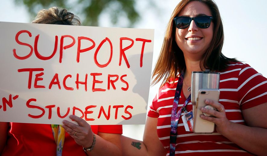 """FILE - In this April 11, 2018, file photo, Stefanie Lowe, a teacher at Tuscano Elementary School, smiles as she joins other teachers, parents and students as they stage a """"walk-in"""" for higher pay and school funding in Phoenix. Tens of thousands of Arizona teachers are poised to participate in a statewide job action this week in an unprecedented walkout to demand more funding for public education. (AP Photo/Ross D. Franklin, File)"""