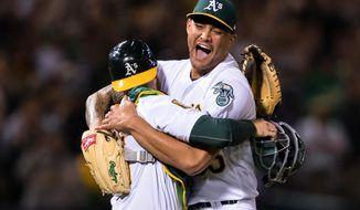 """FILE - In this April 21, 2018, file photo, Oakland Athletics starting pitcher Sean Manaea, right, celebrates with catcher Jonathan Lucroy after pitching a no-hitter against the Boston Red Sox during a baseball game in Oakland, Calif. I'm looking forward to seeing what he's going to do the rest of the season,"""" A's catcher Jonathan Lucroy said. """"The way he's thrown so far this year is really, really special. ... He's definitely looking good."""" (AP Photo/John Hefti, File)"""