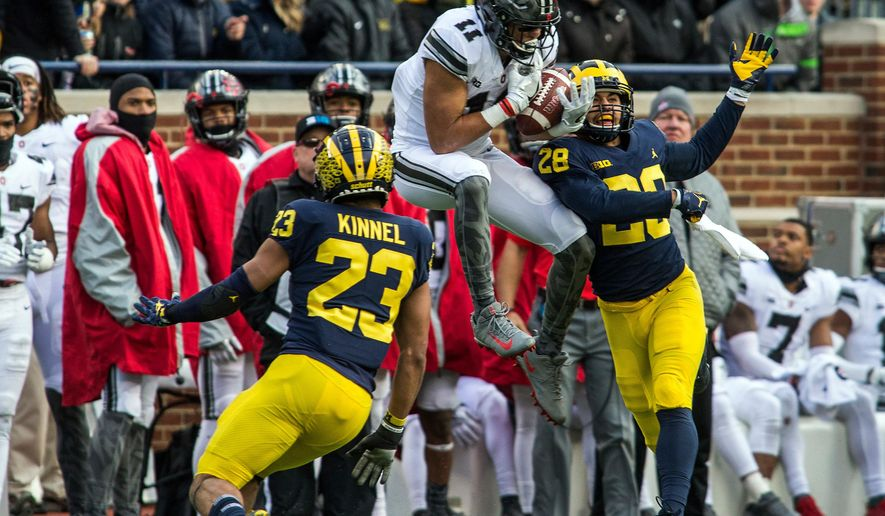FILE - In this Nov. 25, 2017, file photo, Ohio State wide receiver Austin Mack (11) makes a catch defended by Michigan defensive backs Tyree Kinnel (23) and Brandon Watson (28), in the third quarter of an NCAA college football game in Ann Arbor, Mich. The junior was the fifth-leading receiver last year with 24 catches for 343 yards and two TDs. (AP Photo/Tony Ding, File)