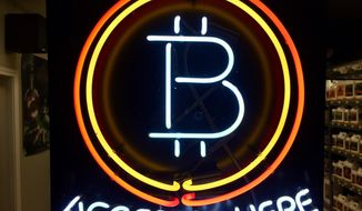 FILE - In this Feb. 7, 2018 File, photo, a neon sign hanging in the window of Healthy Harvest Indoor Gardening in Hillsboro, Ore., shows that the business accepts bitcoin as payment. The Wisconsin Ethics Commission is considering a policy guiding what to do about political contributions made in bitcoin and other cryptocurrencies. Bitcoin is gaining in popularity as a type of privately issued digital money. The Wisconsin Ethics Commission is holding a hearing Tuesday, April 24, 2018, in response to February request from the Libertarian Party of Wisconsin for public input and a policy on the use of campaigns accepting cryptocurrencies and making payments with them.(AP Photo/Gillian Flaccus File)