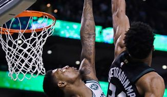 Boston Celtics guard Marcus Smart, left, blocks a shot by Milwaukee Bucks forward Giannis Antetokounmpo during the first quarter of Game 5 of an NBA basketball first-round playoff series in Boston, Tuesday, April 24, 2018. (AP Photo/Charles Krupa)