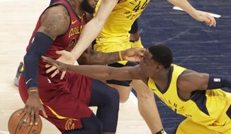 Cleveland Cavaliers forward LeBron James (23) is defended by Indiana Pacers guard Darren Collison (2) and forward Bojan Bogdanovic (44) during the first half of Game 4 of an NBA basketball first-round playoff series in Indianapolis, Sunday, April 22, 2018. (AP Photo/Michael Conroy)