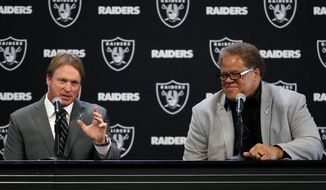 FILE - In this Jan. 8, 2018, file photo, Oakland Raiders new head coach Jon Gruden, left, answers a question next to general manager Reggie McKenzie during an NFL football news conference in Alameda, Calif. The approach McKenzie takes into the NFL draft is no different with Gruden as coach than it was in previous years with Jack Del Rio and Dennis Allen at the helm. (AP Photo/Marcio Jose Sanchez, File)