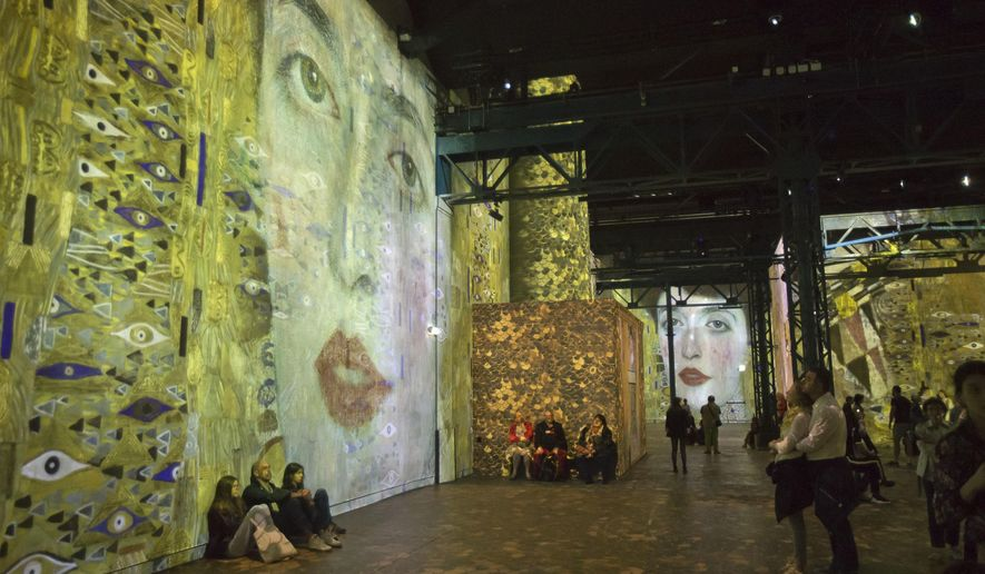People look at the Austrian painter Gustav Klimt art projection at the l'Atelier des Lumieres gallery in Paris, France, Tuesday, April 24, 2018. A digital gallery in Paris is breaking new ground by exhibiting art as an immersive experience for visitors can walk 'inside' paintings that are vividly projected around a warehouse. (AP Photo/Michel Euler)