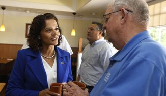FILE - In this April 10, 2018, file photo, Democratic candidate for the Arizona 8th Congressional District special election, Dr. Hiral Tipirneni, left, talks with a supporter at a local restaurant in Sun City, Ariz. Tipirneni is running against former Arizona Republican state Sen. Debbie Lesko in a special election, Tuesday, April 24, to fill the seat vacated by Republican Rep. Trent Franks. (AP Photo/Ross D. Franklin, File)