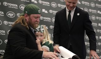 New York Jets center Nick Mangold, left, holds his 3-year-old daughter, Eloise, while signing a contract as team owner Christopher Johnson looks on during a news conference making his official retirement from NFL football, Tuesday, April 24, 2018, in Florham Park, N.J. Mangold announced his retirement a week earlier in a post on Twitter. He was selected to seven Pro Bowls and was twice a first-team All-Pro during his 11-year career. (AP Photo/Julio Cortez)