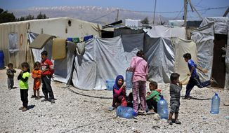 This Monday, April 23, 2018 photo, Syrian refugee children play outside their family tents at a Syrian refugee camp in the town of Bar Elias, in Lebanon's Bekaa Valley. A leading international rights group and the U.N.'s refugee agency say Lebanese authorities have been evicting Syrian refugees from towns and camps in Lebanon without any legal basis. (AP Photo/Bilal Hussein)