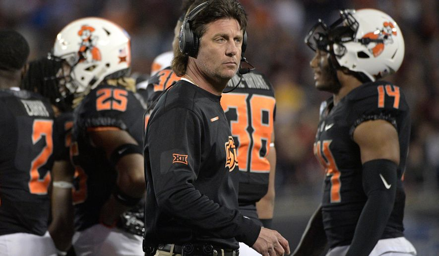 FILE - In this Dec. 28, 2017, file photo, Oklahoma State head coach Mike Gundy, center, walks back to the sideline after a huddle on the field during the first half of the Camping World Bowl NCAA college football game against Virginia Tech, in Orlando, Fla. For the first time in more than three years, Oklahoma State coach Mike Gundy will have a new starting quarterback. Mason Rudolph started 41 games for the Cowboys and left with many of the most significant school records.Taylor Cornelius appears ready to step in. The 6-foot-6, 232-pound senior has taken control of the position during the spring.(AP Photo/Phelan M. Ebenhack, File)