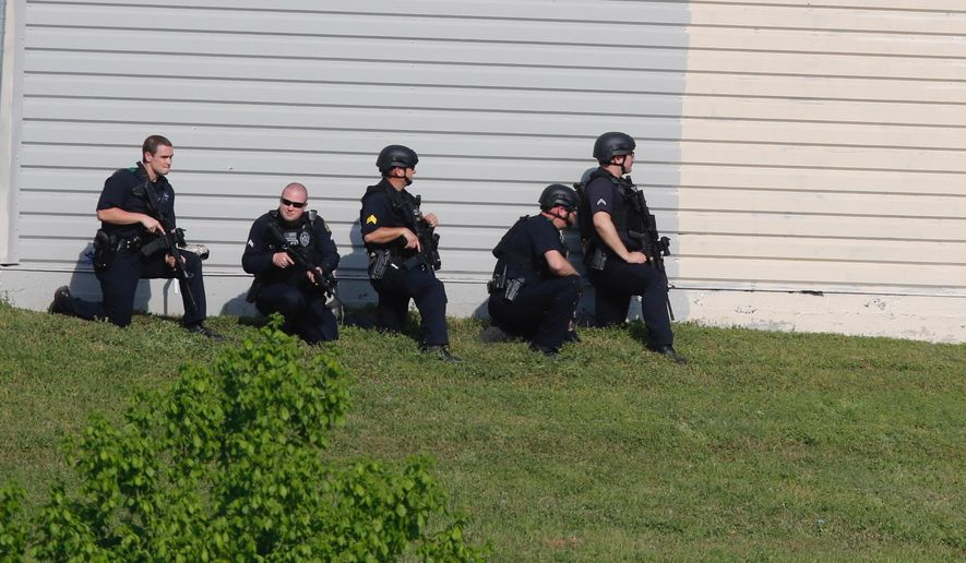 Dallas Police look for a suspect in the shooting of two police officers Tuesday afternoon April, 24,2018. Police are near ExtraSpace Storage, south of Home Depot. (Ron Baselice/The Dallas Morning News via AP)