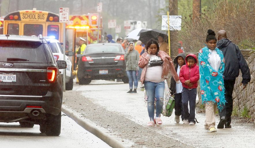 A family walks away from the scene after a school bus was involved in a multi-vehicle crash  Monday, April 23, 2018, in Cincinnati. (Cameron Knight/The Cincinnati Enquirer via AP)