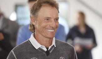 Senior PGA Championship defending champion Bernhard Langer smiles while talking to officials during media day for the 2018 golf tournament at Harbor Shores Golf Course in Benton Harbor, Mich., Monday, April 23, 2018. Langer announced that he will not be competing in this year's championship because his son is graduating from high school the very same weekend. (Don Campbell/The Herald-Palladium via AP)/The Herald-Palladium via AP)