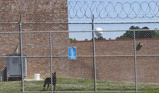 In this April 10, 2018 photograph, a guard dog roams the perimeter of the Rankin County Detention Center in Brandon, Miss. Mississippi inmates waiting for trial often spend months or even years in local jails. A new survey provided exclusively to The Associated Press shows more than one-third of all of those jailed before trial had a stay of more than 90 consecutive days. More than 500 have been in jail longer than a year. (AP Photo/Rogelio V. Solis)