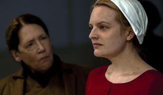 "This image released by Hulu shows Ann Dowd, left, and Elisabeth Moss in a scene from the series, ""The Handmaid's Tale,"" returning for a second season on April 25. (George Kraychyk/Hulu via AP)"