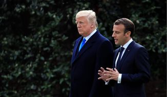 President Donald Trump and French President Emmanuel Macron walk from the Oval Office to a tree planting ceremony on the South Lawn at the White House in Washington, Monday, April 23, 2018. (AP Photo/Manuel Balce Ceneta)