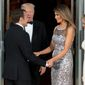 President Donald Trump and first lady Melania Trump greet French President Emmanuel Macron and his wife Brigitte Macron as they arrive for a State Dinner at the White House.