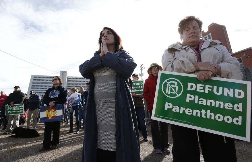 Participants in an anti-abortion rally hold signs and pray as they listen to a member of Christian clergy read from the Bible in front of Planned Parenthood of the Rocky Mountains in Denver on Feb. 11, 2017. (Associated Press) **FILE**
