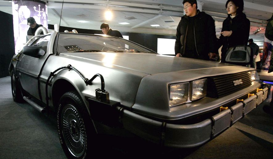 """FILE - In this Saturday, March 5, 2005, file photo, visitors look at a Delorean used in the U.S. movie """"Back to the Future,"""" at International Classic Cars China Tour 2005 in Shanghai. A settlement in a lawsuit over the car used in the 1985 film """"Back to the Future"""" has hit a snag. In 2014, the widow of automaker John DeLorean sued a Texas company she said has been illegally using the DeLorean name for years. The two sides in the lawsuit reached a preliminary settlement in June 2015, that would pay an undisclosed amount of money to Sally DeLorean, but her attorney has written a letter to the judge alleging the company's lawyers were trying to change the settlement at the last minute. (AP Photo/Eugene Hoshiko, File)"""