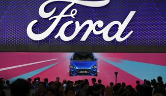 Visitors and journalists crowd near a Ford Focus on display at the Ford exhibit during the media day for the China Auto Show in Beijing, Wednesday, April 25, 2018. Volkswagen and Nissan have unveiled electric cars designed for China at a Beijing auto show that highlights the growing importance of Chinese buyers for a technology seen as a key part of the global industry's future. (AP Photo/Andy Wong)