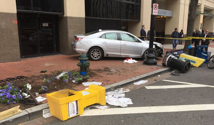 After being struck by a pickup truck taking a wide turn, a driver lost control of his silver Chevrolet sedan and careened onto the sidewalk Tuesday, hitting four pedestrians who police say are being treated for serious injuries. [April 24, 2018] (Photo courtesy of D.C. Fire and Emergency Services)