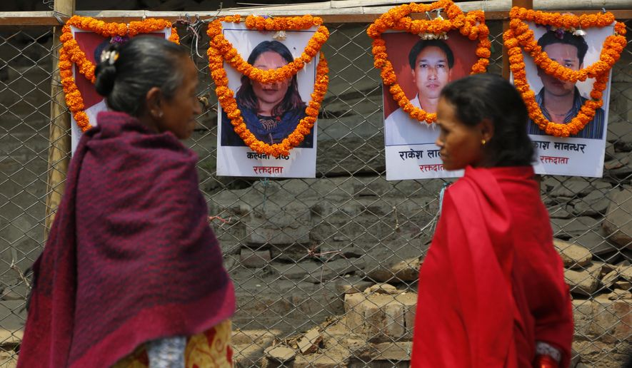 Nepalese women look at portraits of victims of the 2015 earthquake during a function to mark the third anniversary of the earthquake in Kathmandu, Nepal, Wednesday, April 25, 2018. The violence of the 7.8-magnitude earthquake  killed nearly 9,000 people and left countless towns and villages across central Nepal in shambles. (AP Photo/Niranjan Shrestha)