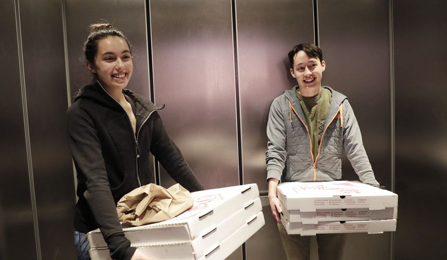 In this April 22, 2018, file photo, New York University's Washington Square News creative director Rachel Buigas-Lopez, left, and managing editor Sayer Devlin haul pizzas in an elevator after ordering them while meeting a middle-of-the night deadline at the newspaper's headquarters in New York. College journalists are speaking up for themselves in a coordinated campaign to combat some of the same forces that have battered newspapers across the country. More than 100 college newsrooms across the U.S., including the Washington Square News, are using social media campaigns, public awareness events and editorials Wednesday, April 25 to call attention to the important roles they play. (AP Photo/Kathy Willens)
