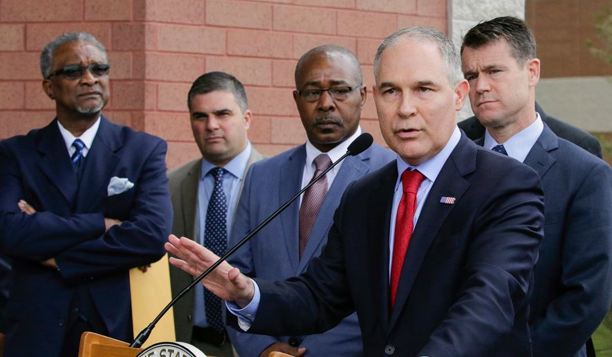 """In this April 19, 2017, file photo, Environmental Protection Agency Administrator Scott Pruitt speaks at a news conference with Pasquale """"Nino"""" Perrotta, second from left, in East Chicago, Ind. Perrotta, the security chief for the head of the Environmental Protection Agency, worked on the side as a private investigator for the owner of a tabloid news company with close ties to President Donald Trump. (AP Photo/Teresa Crawford, File)"""